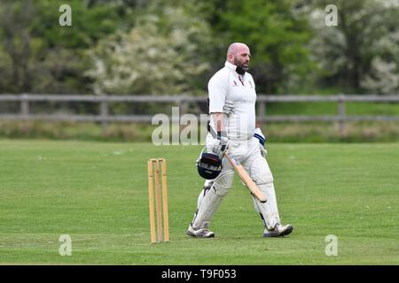 A batsman returns to the pavilion after being bowled out in the Derbyshire and Cheshire League match between Birch Vale and Thornsett, and Hazel Grove. - Stock Photo