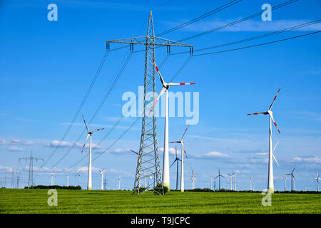 Overhead power lines and wind engines on a sunny day seen in Germany - Stock Photo