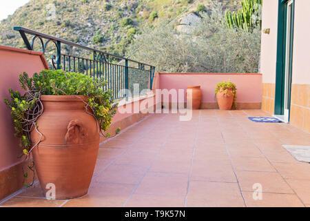 Ceramic vases for olive oil adorn the balconies in Sicily - Stock Photo