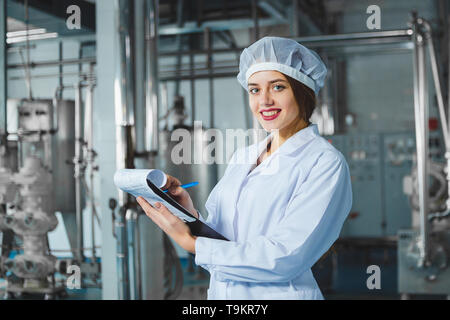 A young beautiful girl in white overalls makes notes in a tablet on the background of equipment of a food processing plant. Quality control in product - Stock Photo