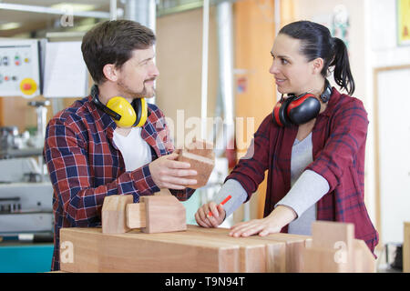experienced carpenters in work clothes making a wooden furniture - Stock Photo
