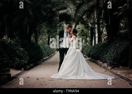 Groom and hug and kiss bride in palm grove. Wedding day for two. Lovely weeding couple - Stock Photo