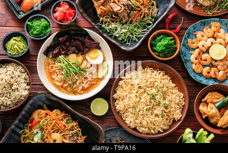 Assortment of Chinese food on wooden table - Stock Photo