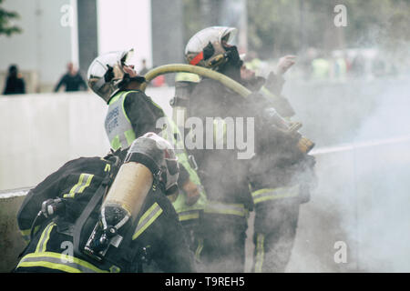 Reims France May 18, 2019 View of firefighters extinguishing a construction hut burned by rioters during protests of the Yellow Jackets in the streets - Stock Photo