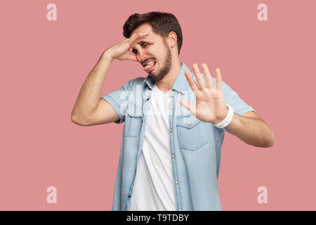 Portrait of bored or confused handsome bearded young man in blue casual style shirt standing, pinching his nose and showing stop gesture hand sign. in - Stock Photo