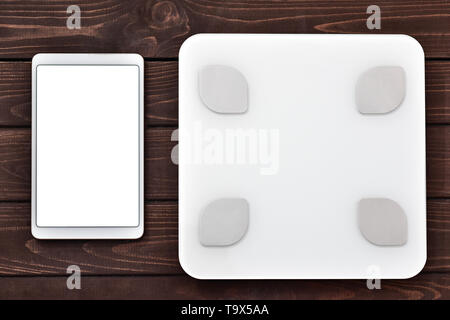 Glycemic index Fitness and weight loss concept, white scale and tablet on wooden table, top view, - Stock Photo