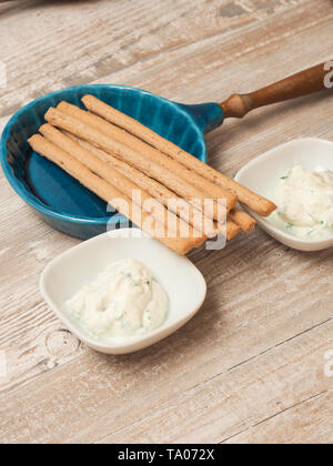Fresh organic cream cheese with chives and parsley served with organic spelt sticks - Stock Photo