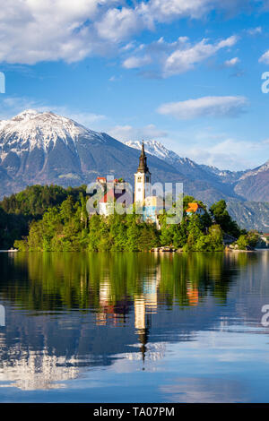 Church on island reflected in waters of Bled Lake, Slovenia. Beautiful sunsen. Julian Alps in background - Stock Photo