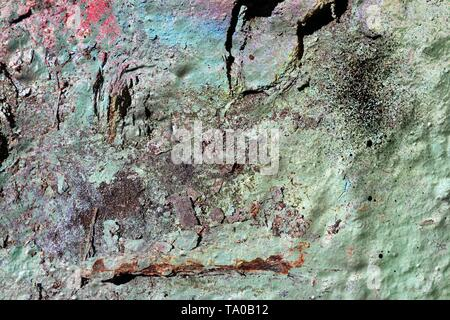 Detailed clöse up surface of colorful peeling sprayed paint on weathered concrete walls - Stock Photo