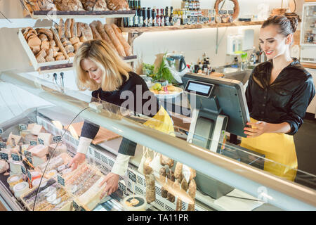 Two saleswomen selling groceries in deli - Stock Photo