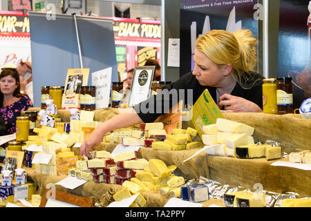 Woman working on stall selling variety of cheeses, arm outstretched  reaching for portion of cheese - Great Yorkshire Show, Harrogate, England, UK. - Stock Photo