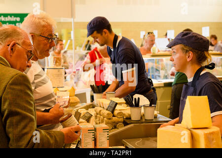 People working on cheese stall selling variety of cheeses (female trader talking to potential customers) -Great Yorkshire Show, Harrogate, England, UK - Stock Photo