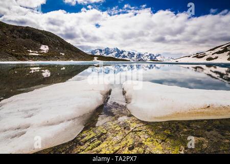 Ice blocks on the shore of alpine lake Lej da la Tscheppa during thaw, St. Moritz, Engadin, canton of Graubunden, Switzerland - Stock Photo