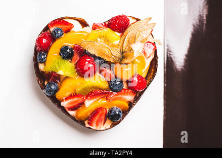 Heart shaped fruit sponge cake, Fruit Tart on a square plate on table. Healthy confectionery background. space for text - Stock Photo