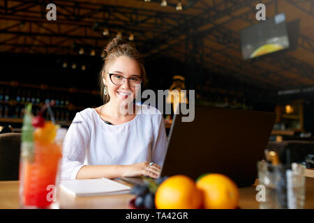 Businesswoman working remotely at cafe with headset and laptop. Mixed race female performing business negotiations on conference video chat. Telecommu - Stock Photo