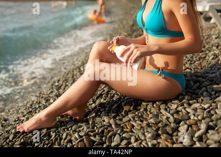 Slim woman tanned lower body in shape lying on pebble beach near sea waves and surf with sunblock cream bottle. Girl applies water resistant sunscreen - Stock Photo