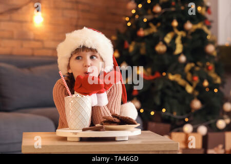 Cute little girl in Santa hat with hot chocolate and cookies at home on Christmas eve - Stock Photo