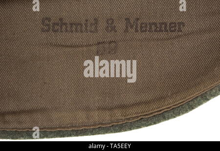 A garrison cap for enlisted men/NCOs of Waffen-SS infantry units depot piece Field-grey woollen cloth in SS 'boat-shaped' cut with stitched-in cap piping in base cloth, brown cotton liner with stamping 'Schmid & Menner' and size 59. Hand-stitched, silver-grey on black woven BeVo insignia, white soutache chevron. Unused, with moth traces. historic, historical, 20th century, 1930s, 1940s, Waffen-SS, armed division of the SS, armed service, armed services, NS, National Socialism, Nazism, Third Reich, German Reich, Germany, military, militaria, utensil, piece of equipment, uten, Editorial-Use-Only - Stock Photo