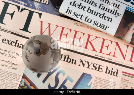 The Financial Times newspaper photographed with a glass globe positioned on top. - Stock Photo