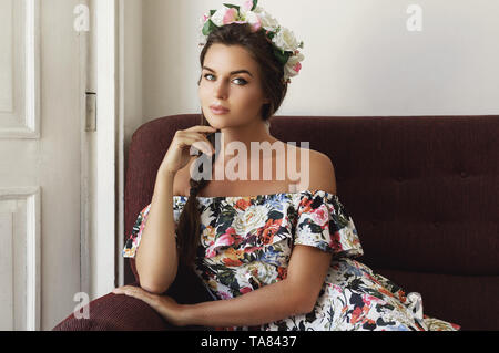 Portrait of young woman in beautiful dress is sitting on the vintage sofa - Stock Photo