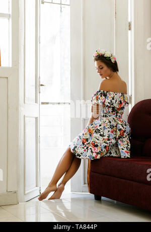 Happy woman in beautiful dress is sitting on the vintage sofa in old house - Stock Photo