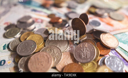 Top view of various coins spreaded on the the table. A lot of metal coins from different countries in the pile. - Stock Photo