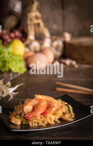 Thai fried noodles or pad thai with shrimp on black plate placed on the wood table there are chopsticks, eggs, lettuce, garlic, bean sprouts, shallot  - Stock Photo