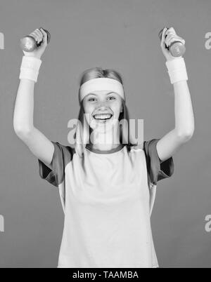Woman exercising with dumbbells. Easy exercises with dumbbells. Workout with dumbbells. Ultimate upper body workout for women. Girl hold dumbbells wear bright wristbands. Vintage sport concept. - Stock Photo