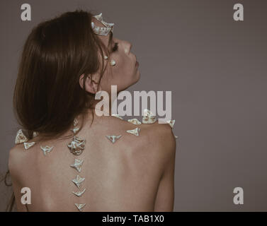 Girl with fantasy style make up. Woman with thorns on back shoulders looks like fantasy creature. Scary fairy tail character. Halloween ideas concept - Stock Photo