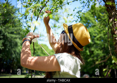 Happy close up of a Latina Brazilian woman wearing a straw hat outside in a park during a birthday celebration in spring sunshine - Stock Photo