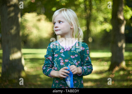Cute young girl with long blonde hair wearing a green flower dress standing in a park in spring sunshine - Stock Photo