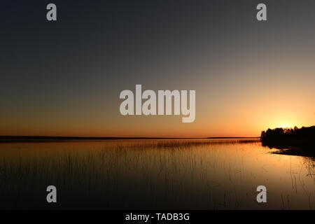 Sunset golden hour the sun in the sky sets behind the trees of the lake shoreline cape - Stock Photo