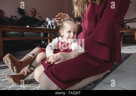 Portrait of girl with mother in living room and grandfather in background - Stock Photo