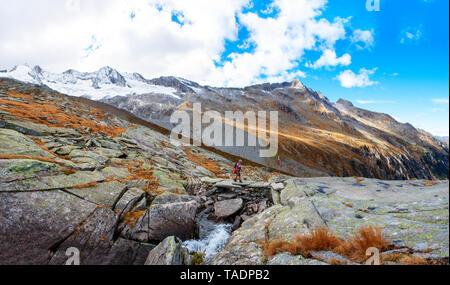 Austria, Salzburg State, High Tauern National Park, Zillertal Alps, woman hiking on rocks - Stock Photo