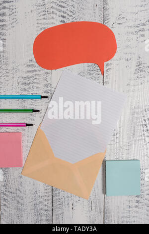 Envelop speech bubble paper sheet ballpoints notepads wooden background - Stock Photo