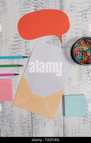 Envelop speech bubble paper sheet ballpoints notepads clips wooden back - Stock Photo