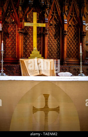 Riga, Latvia - May 18, 2018. Riga Luther Church. Church altar with cross and bible before wedding ceremony. Open bible on altar before worship. Interi - Stock Photo