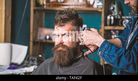 Stylish haircut concept. Hands of barber with clipper close up. Client with beard on salon background. Hipster bearded client on strict face getting hairstyle. Barbers hand with hair clipper trimming. - Stock Photo