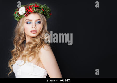 Pretty woman in green fir crown on black background - Stock Photo
