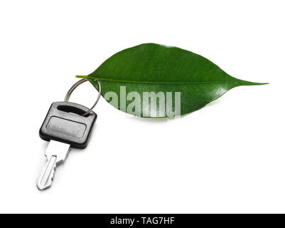 Key from car and green leaf on white background. Ecology concept - Stock Photo