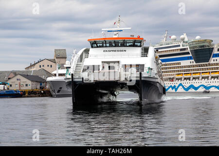 High speed passenger catamaran Ekspressen arriving in the port of Bergen, Norway. In background, cruise ship Aidasol. - Stock Photo