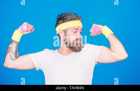 Motivated athlete guy. Sportsman training with dumbbells blue background. Improve your muscles. Man bearded athlete exercising dumbbell. Use weights or dumbbells. Athlete training with tiny dumbbell. - Stock Photo