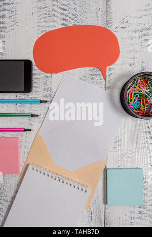 Envelop speech bubble smartphone sheet pens spiral notepads clips wooden - Stock Photo