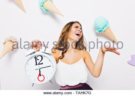 Splendid young woman in white tank-top posing with eyes closed holding clock on decorated background. Studio portrait of excited brunette girl laughing standing in front of wall with toy sweets on it - Stock Photo