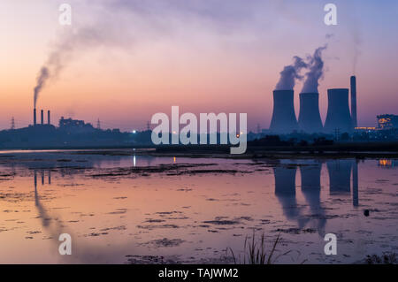 Coal powered thermal power plant emitting smoke and steam from chimney and cooling tower. Reflection of cooling tower and chimney on lake. - Stock Photo
