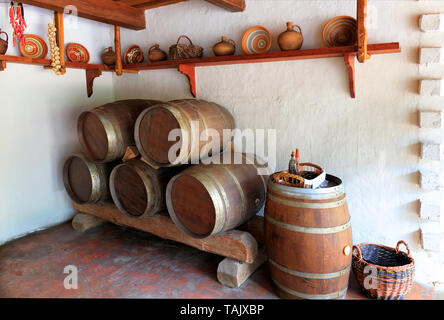 Vintage wooden wine barrels, ceramic painted bowls, plates and jugs on a wooden shelf on the wall, a wicker basket with glassware in the interior of a - Stock Photo
