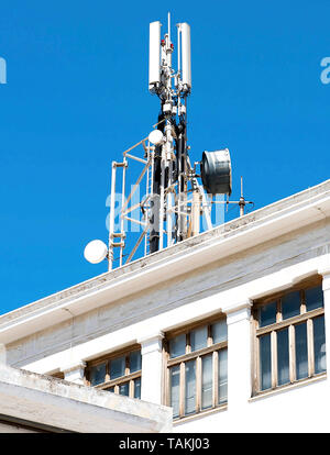 Cell phone telecommunications antennas and repeaters on building against clear blue sky - Stock Photo