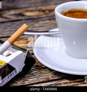 Cup of Fresh Espresso With a Packet of Cigarettes on a Wooden Table Top. - Stock Photo