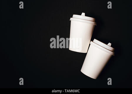 Two paper cups for coffee or tea on black background. Copy space for text. - Stock Photo