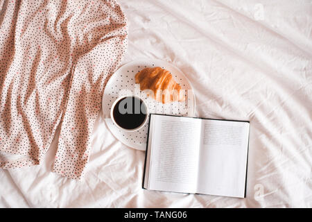 Good morning. Cup of coffee, cake and open book with cute skirt closeup. Top view. - Stock Photo